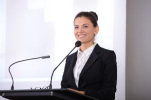 Woman at podium smiling.