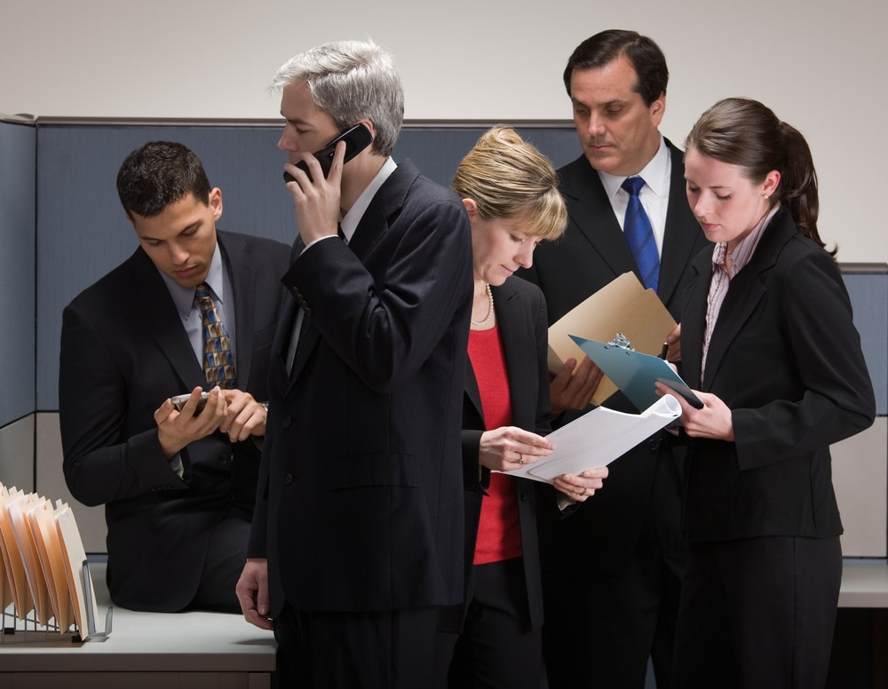 Communicate early during a crisis. Coworkers gathered in a room during a crisis.