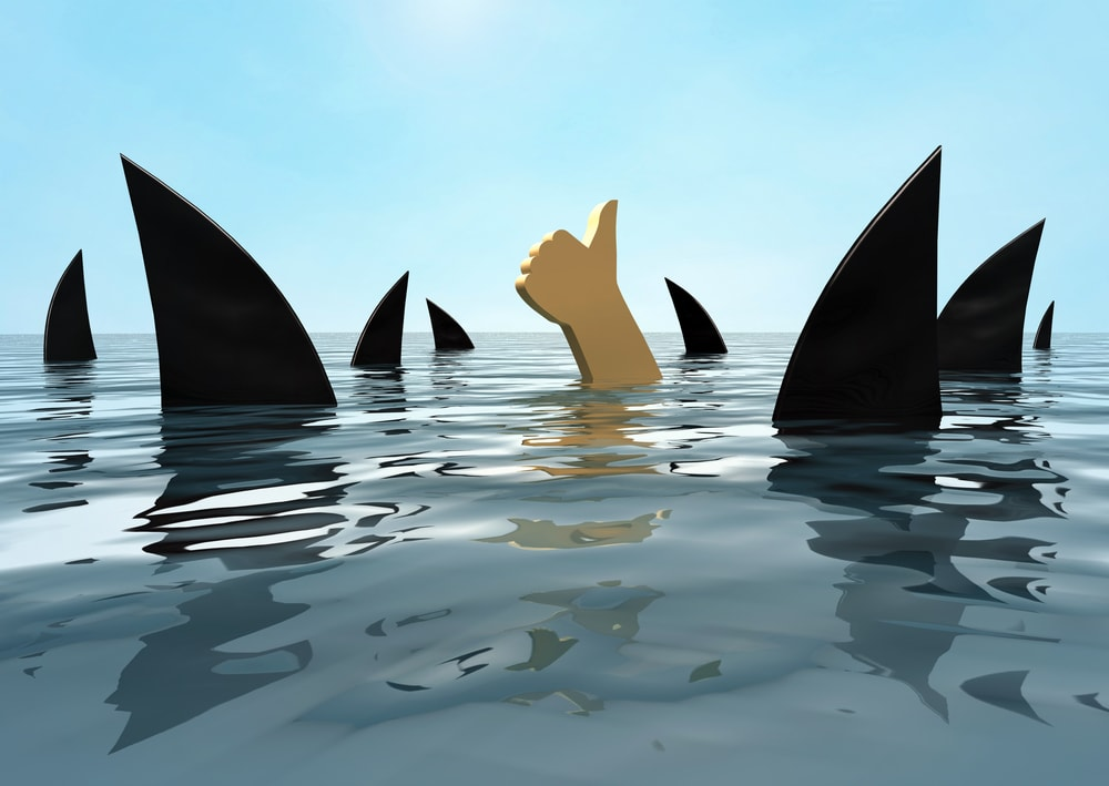 Have a crisis plan so you can stay afloat during a crisis. Person staying afloat among sharks.