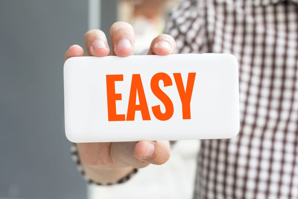 "Person holding a sign that says ""EASY."""