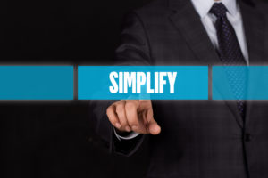 """Finger pointing at the word """"Simplify."""""""