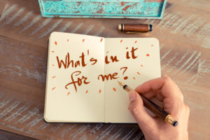 "Open notebook with ""What's in it for me?"" written in it."
