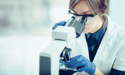How does content marketing apply to a highly educated audience? Woman wearing googles and gloves looking into a microscope.