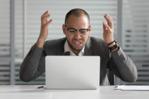 Man wearing glasses in front of laptop with frustrated look and hands raised in frustration.