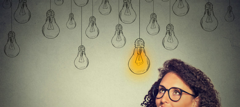 Woman thought leader having idea with a lit bulb by her head.