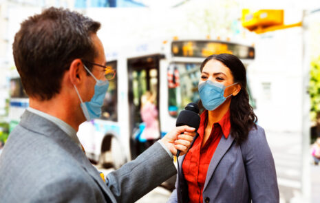 Best spokesperson for a media interview: male reporter with mask on interviews female spokesperson.