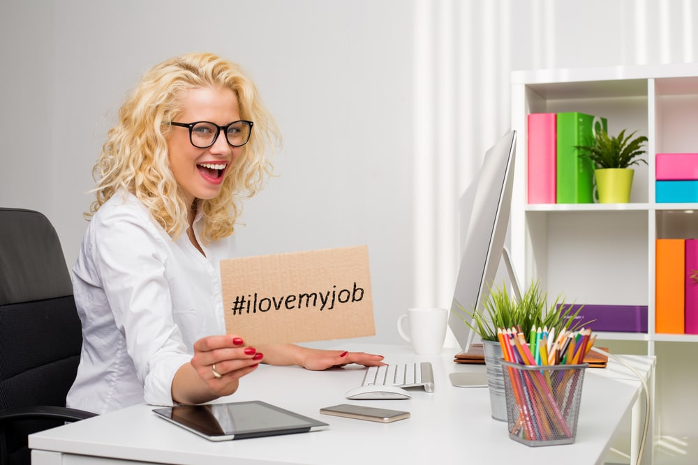 "Woman at desk holding sign that says ""I love my job."""