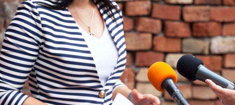 Torso of a woman in front of two microphones for a media interview.