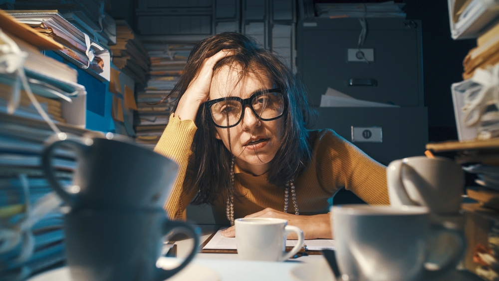 Overwhelmed woman with head on hand siting at desk surrounded by coffee mugs