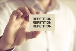 """Person holding a small sign that reads """"repetition"""" 3 times."""