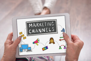 """How do you communicate a clear content strategy and message map to all marketing channels? Person holding tablet that says """"Marketing Channels"""" and has icons of different channels."""