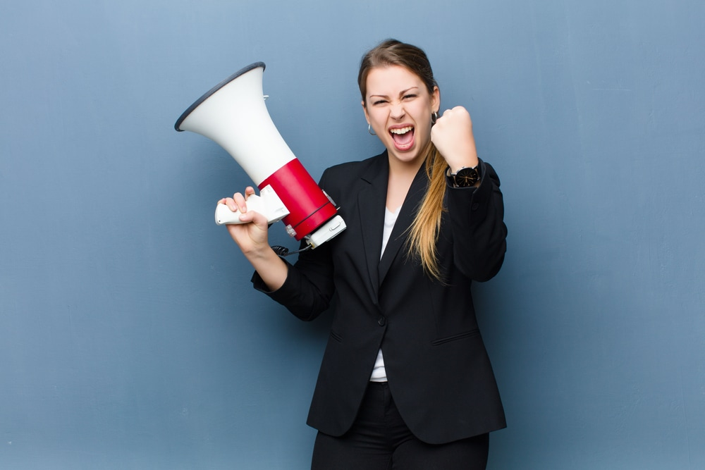 How do you communicate a clear content strategy and message map to all marketing channels? Happy businesswoman holding megaphone