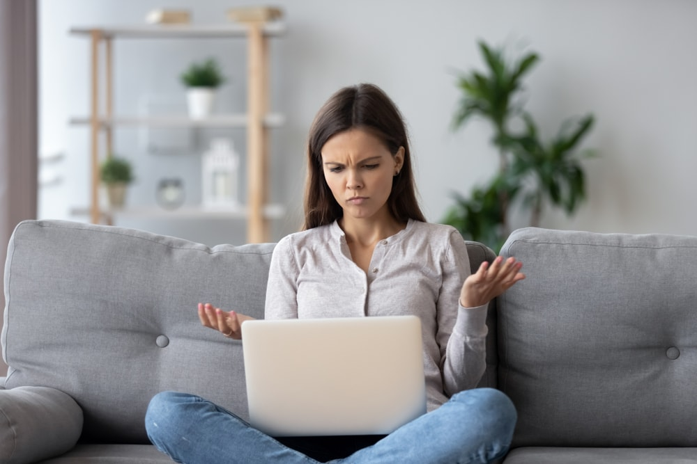 Content personalization - Woman looking at laptop with a confused expression and her hands up in the air--she is displeased with what she sees on laptop.