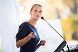 Female business presenter advancing slide.