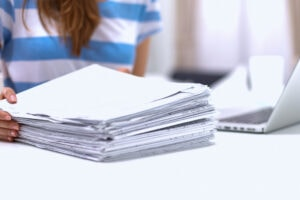 Woman in front of a huge stack of papers to read.