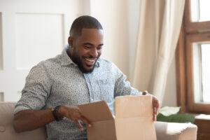 Digital marketing - Smiling black man opening a package.
