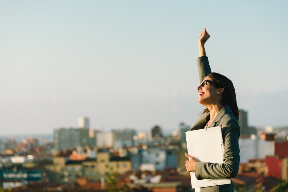 3 tips to help you succeed -Triumphant business woman holding a fist in the air and clutching work with her other hand. Cityscape in background.